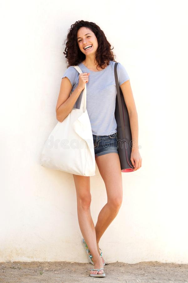 Giovane donna piena del corpo che sorride con la stuoia e la borsa di yoga contro il fondo bianco immagini stock libere da diritti