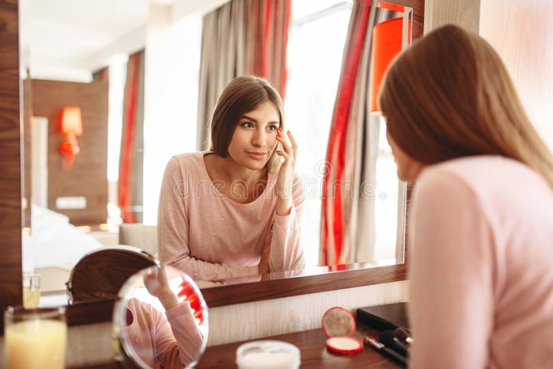Giovane donna in pigiama davanti allo specchio immagini stock libere da diritti