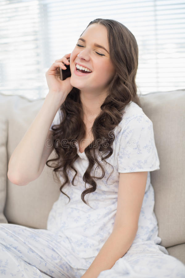 Giovane donna in pigiami che ride sul telefono fotografia stock libera da diritti
