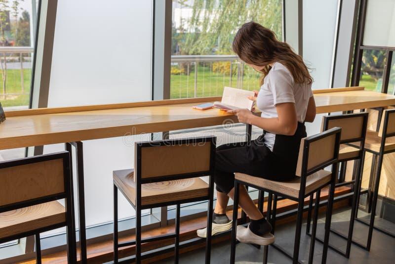 Giovane donna positiva in occhiali alla moda che sogna mentre sedendosi alla tavola con il libro aperto nello spazio coworking al fotografie stock