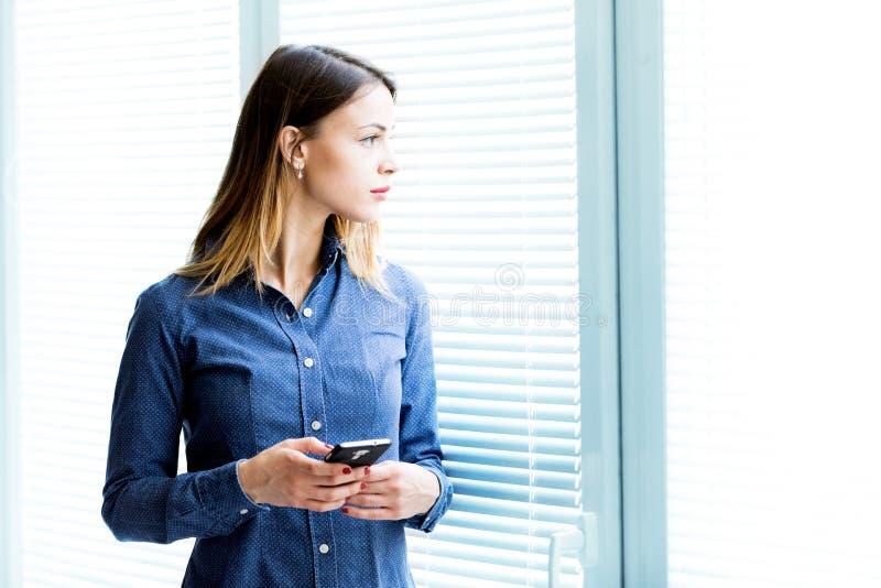 Giovane donna premurosa che fissa attraverso una finestra fotografia stock