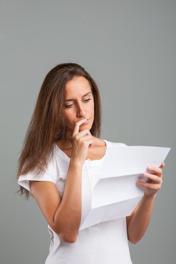 Giovane donna premurosa che legge un documento fotografia stock libera da diritti