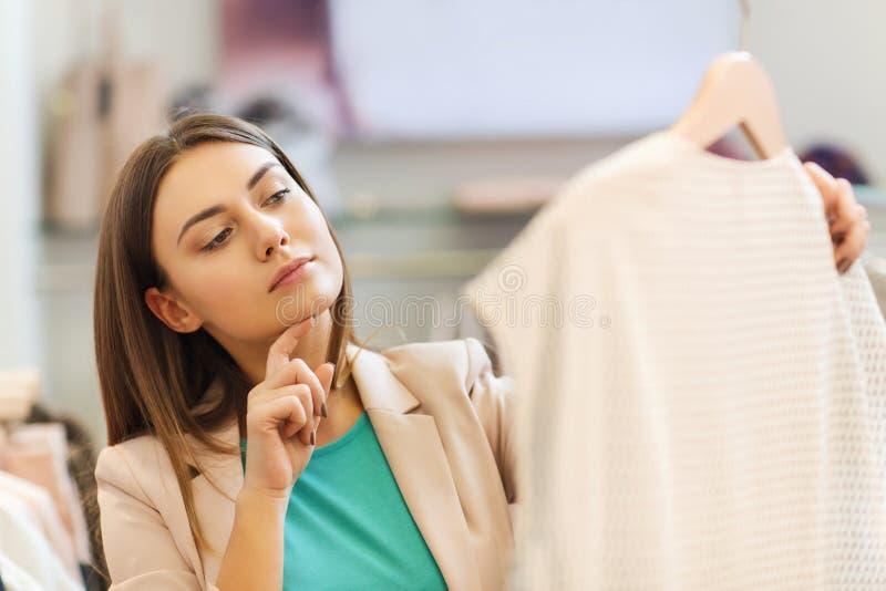 Giovane donna premurosa che sceglie i vestiti in centro commerciale immagine stock