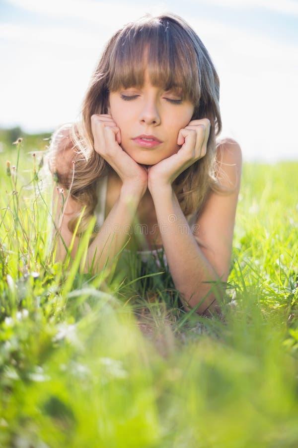 Giovane donna premurosa che si trova sull'erba immagini stock libere da diritti