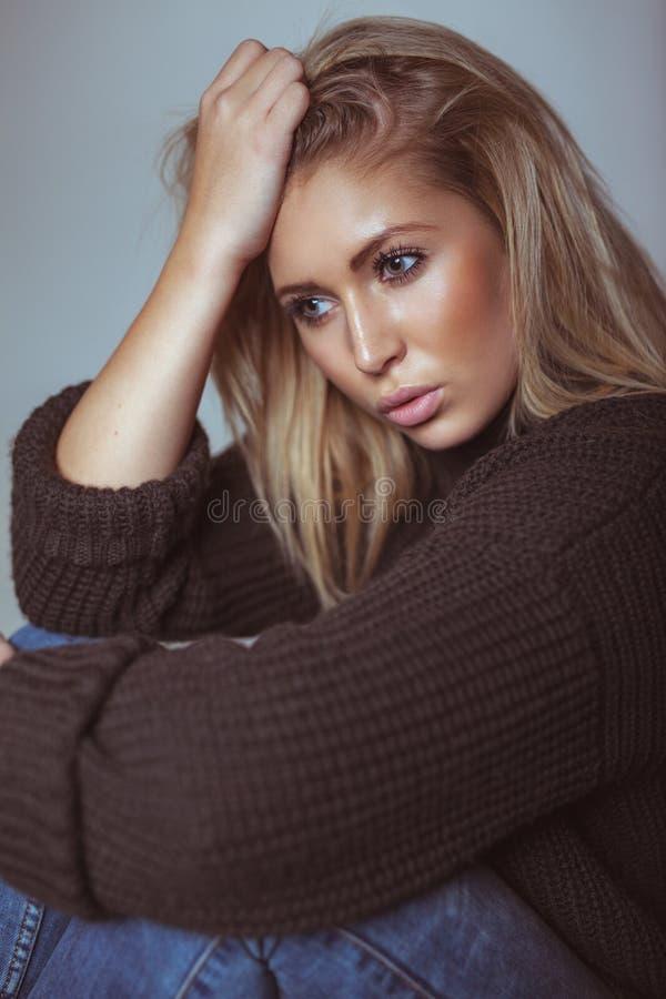 Giovane donna premurosa nel distogliere lo sguardo del maglione fotografie stock libere da diritti