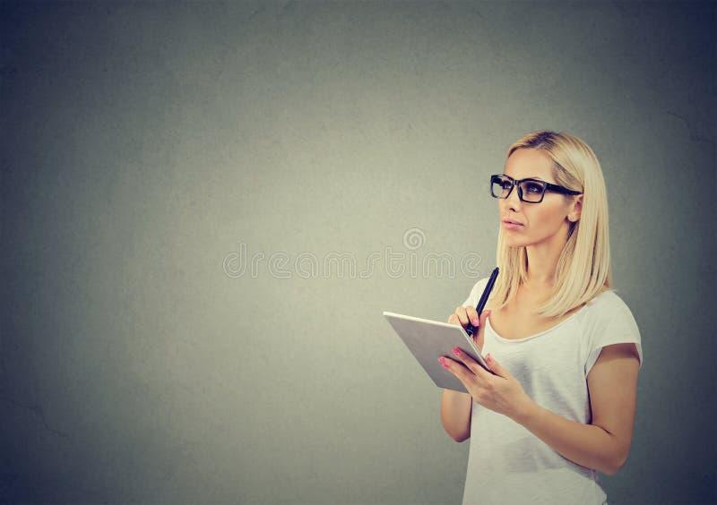 Giovane donna premurosa in vetri con pianificazione del computer della compressa fotografia stock