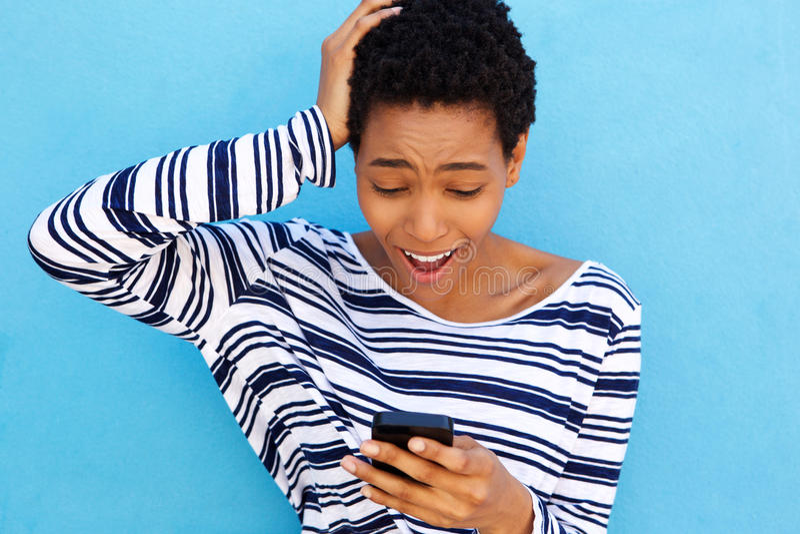 Giovane donna preoccupata che esamina telefono cellulare fotografie stock