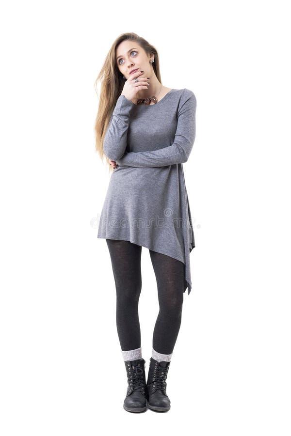 Giovane donna preoccupata in tunica grigia che pensa e che cerca con le mani sul mento immagine stock libera da diritti