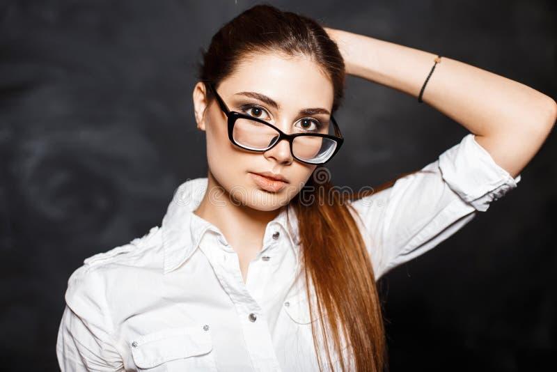 Giovane donna professionale alla moda in vetri e in un blou bianco fotografia stock libera da diritti