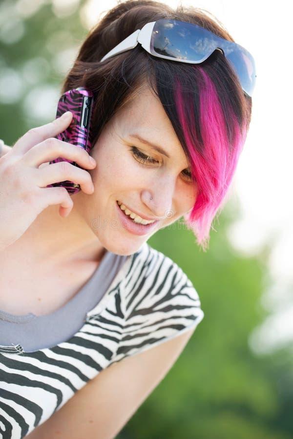 Giovane donna punk su un telefono delle cellule immagine stock