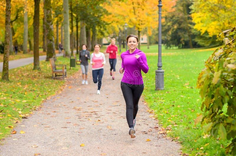 Giovane donna quattro fuori che corre insieme in un parco fotografia stock