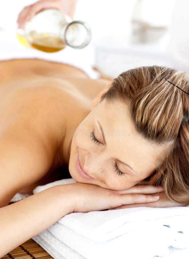 Giovane donna radiante che ha un massaggio posteriore con olio fotografie stock