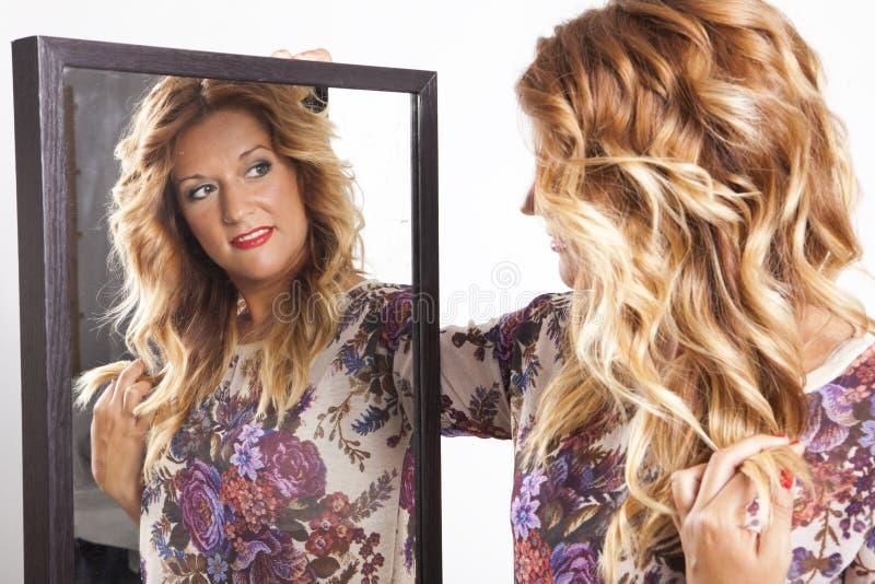 Giovane donna reale che guarda in uno specchio fotografia stock libera da diritti
