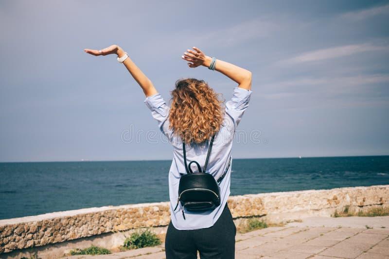 Giovane donna riccia che alza le sue armi su fotografia stock