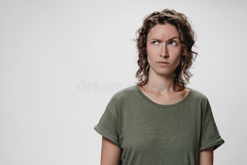 Giovane donna riccia con espressione facciale negativa imbarazzata delle sopracciglia di aumenti immagini stock libere da diritti