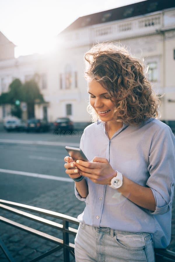 Giovane donna riccia felice che manda un sms e che sorride sullo Smart Phone fotografie stock libere da diritti