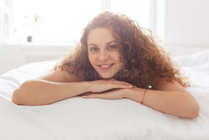 Giovane donna riccia felice con l'aspetto piacevole, bugie sul comfor fotografie stock