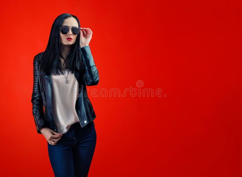 Giovane donna rigorosa con capelli neri in occhiali da sole alla moda fotografia stock