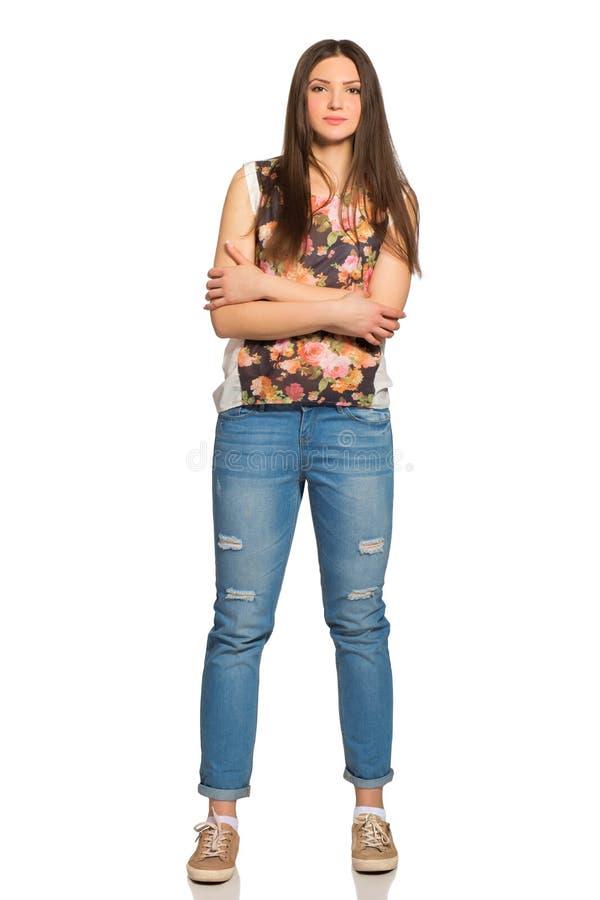Giovane donna rilassata attraente, altezza completa, con le armi attraversate fotografia stock libera da diritti