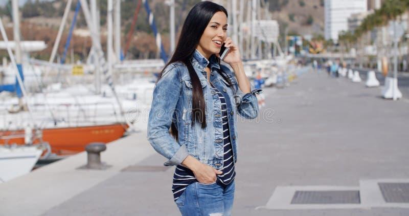 Giovane donna rilassata d'avanguardia che parla su un cellulare immagine stock