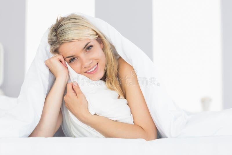 Giovane donna rilassata sorridente che abbraccia cuscino a letto fotografia stock libera da diritti