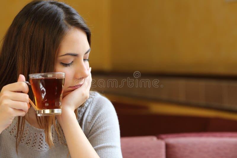 Giovane donna rilassata in una caffetteria che tiene una tazza di tè immagini stock libere da diritti