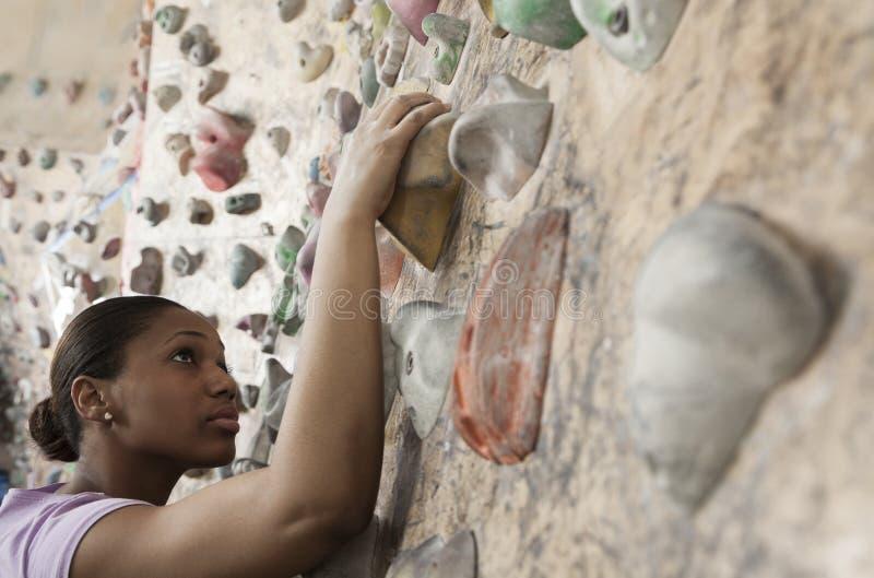Giovane donna risoluta che scala una parete rampicante in una palestra rampicante dell'interno fotografia stock
