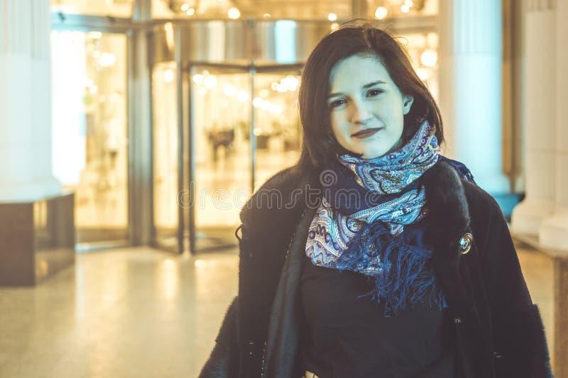 Giovane donna in ritratto della sciarpa alla città di notte fotografia stock