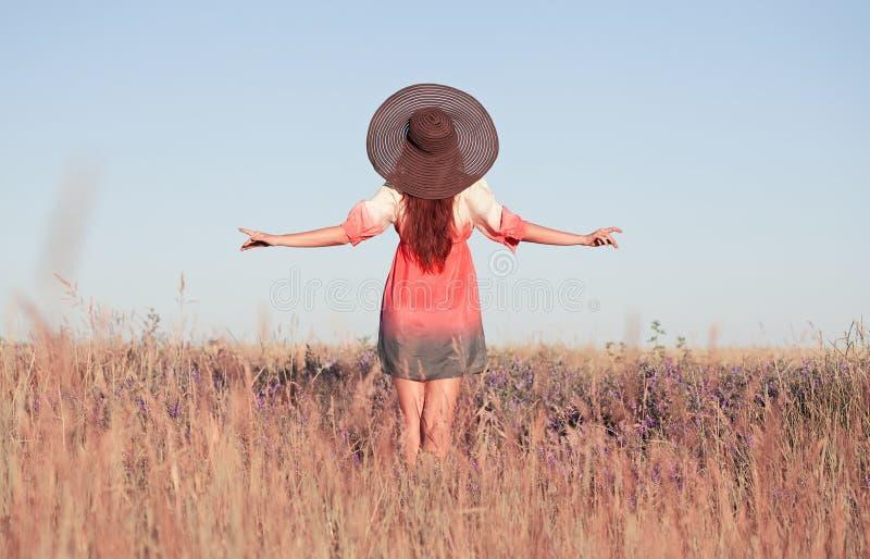 Giovane donna romantica in cappello che sta sul prato nel giorno di estate caldo immagine stock libera da diritti