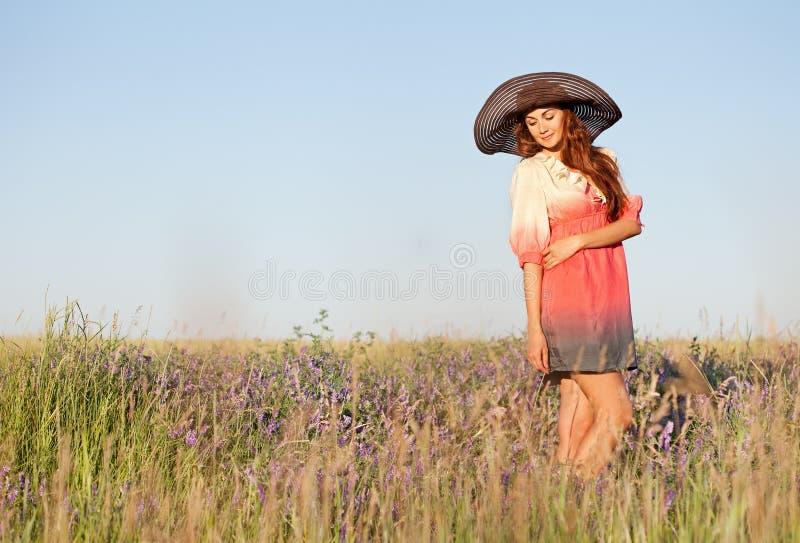 Giovane donna romantica in cappello che sta sul prato nel giorno di estate caldo immagine stock