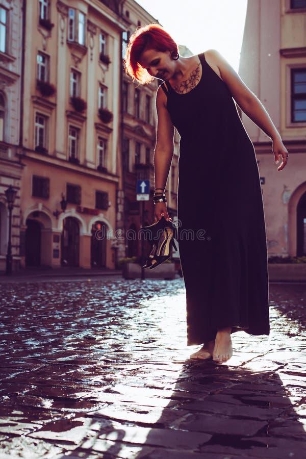 Giovane donna rossa dei capelli che cammina sulle vie di Cracovia, Polonia immagine stock