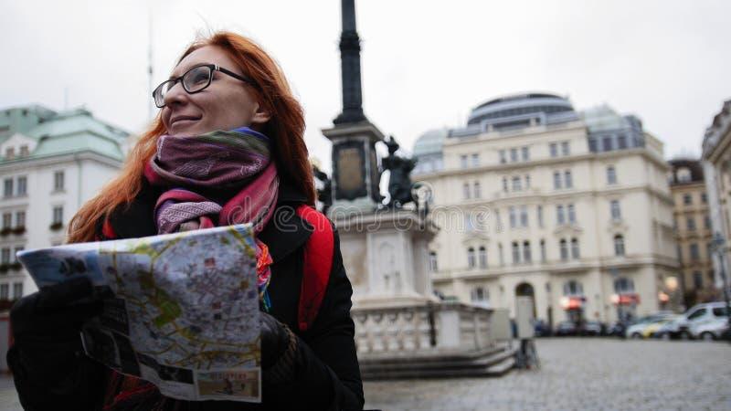 Giovane donna rossa dei capelli che utilizza la mappa della città a Vienna, grandangolare immagini stock