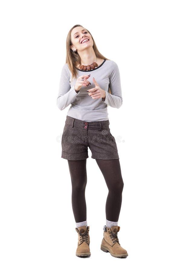 Giovane donna schietta rilassata felice in vestiti autentici di stile dei pantaloni a vita bassa che parla e che gesturing fotografia stock