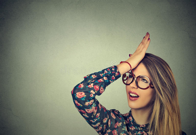 Giovane donna sciocca, schiaffeggiante mano sulla testa che ha duh momento Il rammarico fa torto a fare fotografia stock