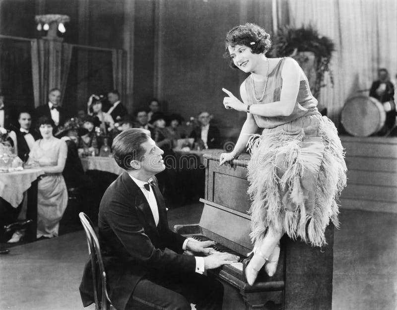 Giovane donna sedendosi sulla cima il piano e parlando con il pianista (tutte le persone rappresentate non sono della proprietà e fotografia stock