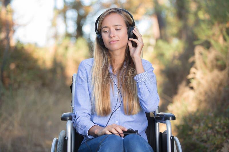 Giovane donna in sedia a rotelle nella foresta di primavera immagini stock