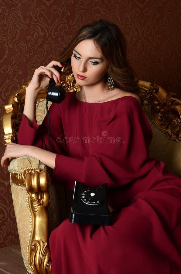 La giovane donna sensuale elegante in un vestito dal chiaretto fotografia stock