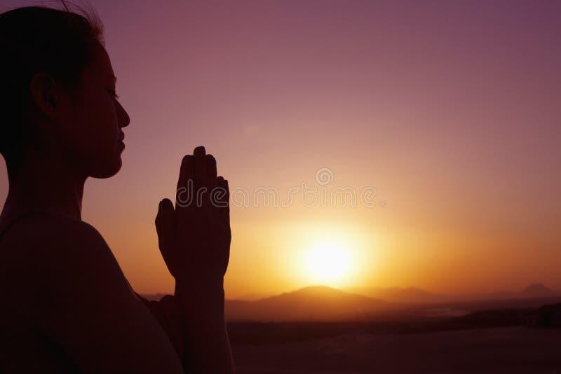 Giovane donna serena con le mani insieme nella posa di preghiera nel deserto in Cina, siluetta, regolazione del sole, profilo fotografia stock