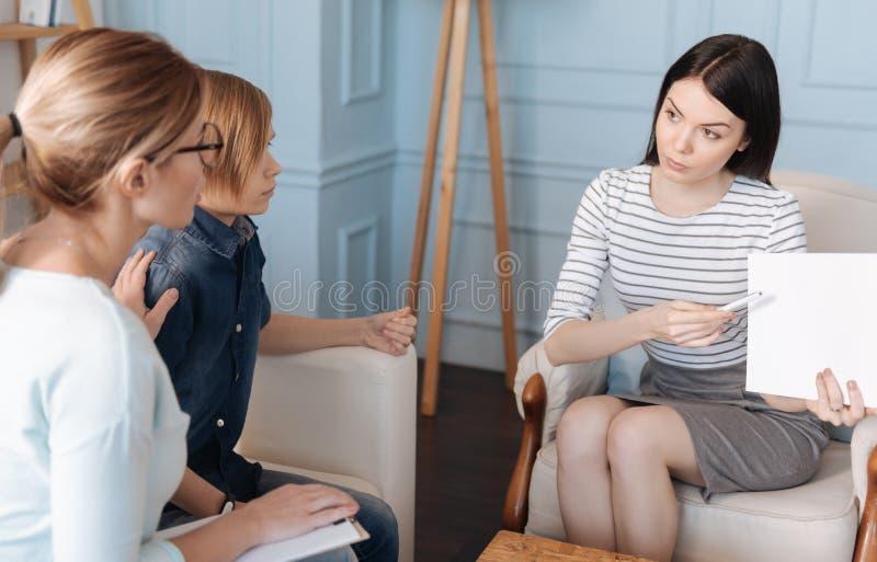 Giovane donna seria che mostra i documenti immagine stock