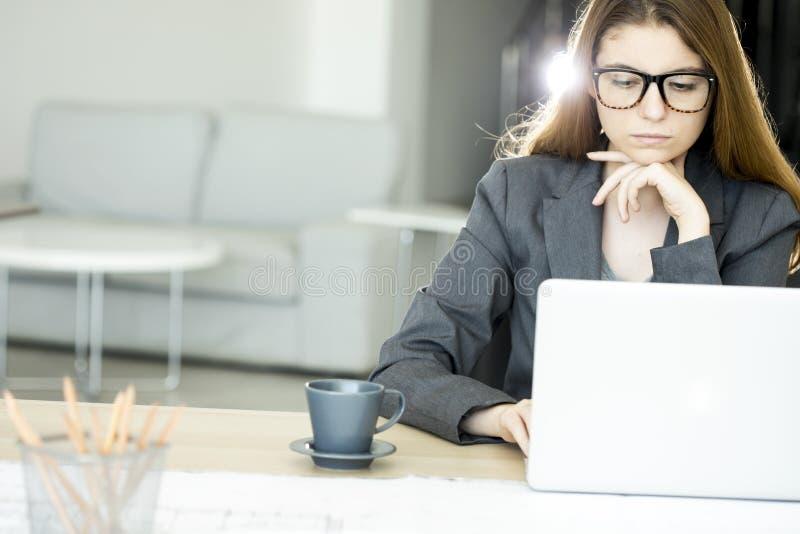 Giovane donna seria che per mezzo del computer portatile immagini stock