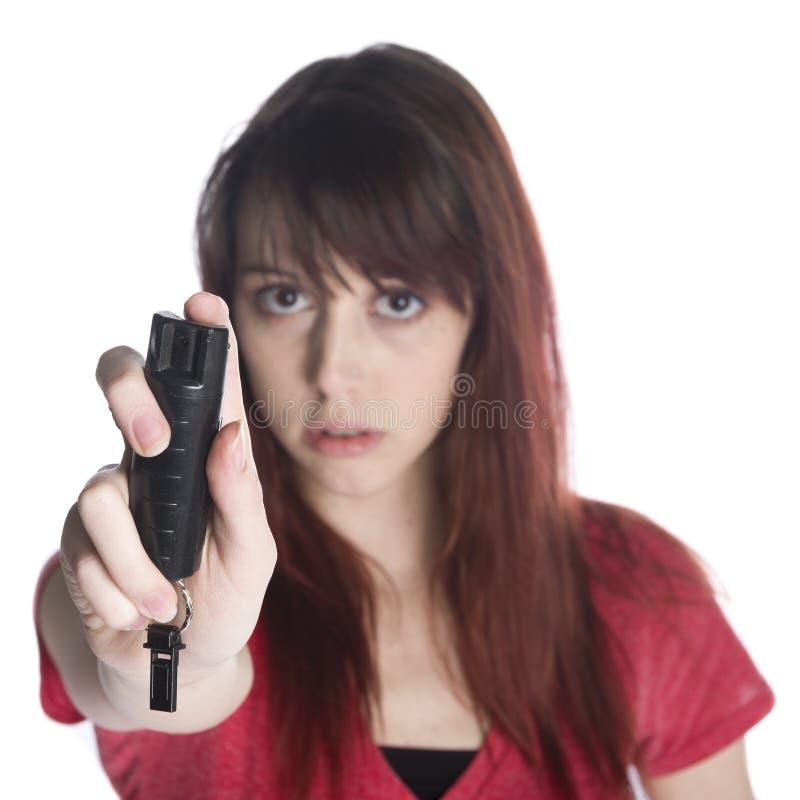 Giovane donna seria che tiene lo spruzzo nero del gas lacrimogeno immagini stock