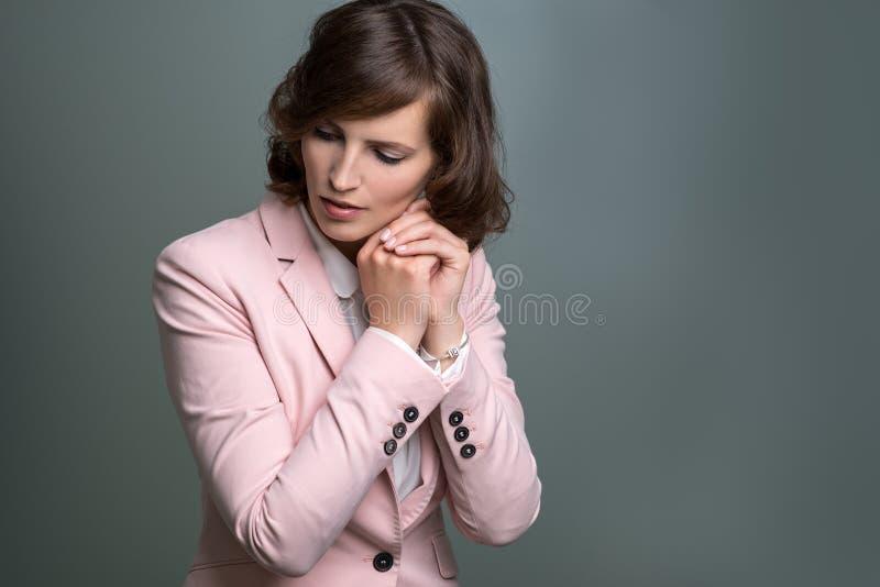 Giovane donna seria con le mani afferrate nella preghiera fotografie stock libere da diritti