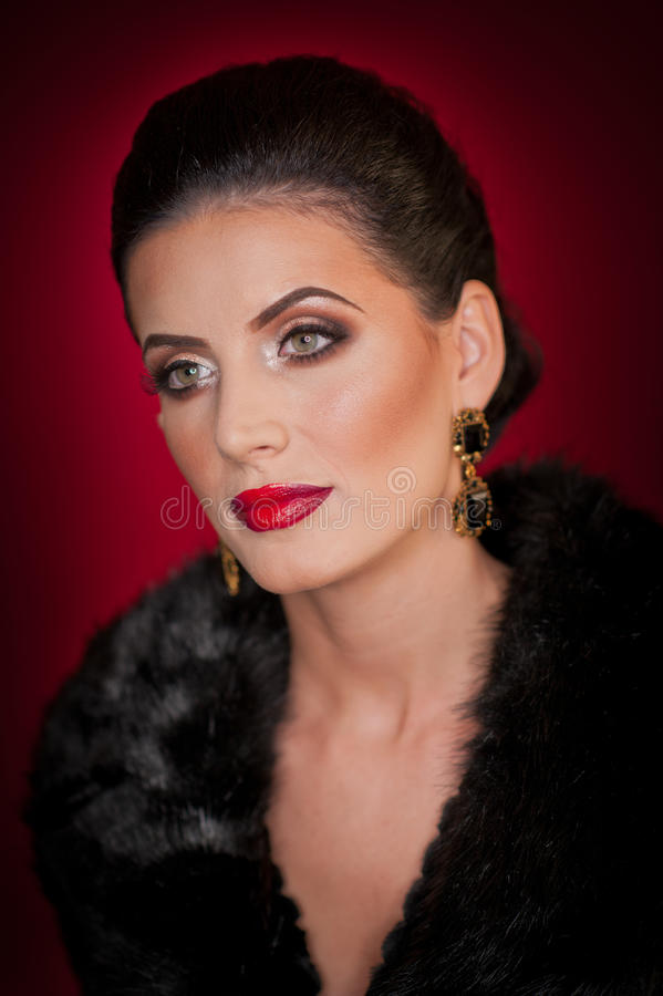 Giovane donna sexy attraente che porta una pelliccia che posa nello studio su fondo porpora scuro Ritratto della femmina sensuale fotografia stock libera da diritti