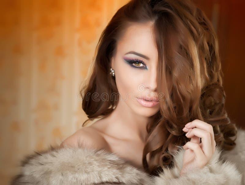 Giovane donna sexy attraente che porta una pelliccia che posa provocatorio dell'interno Ritratto della femmina sensuale con trucc immagini stock libere da diritti