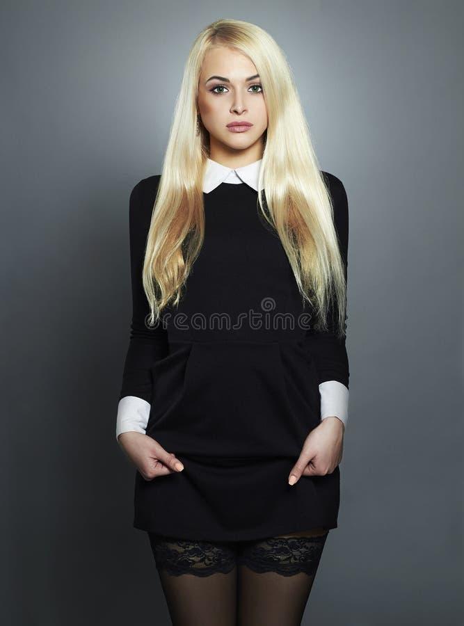Giovane donna sexy bionda Bella ragazza in vestito nero schoolgirl fotografie stock libere da diritti