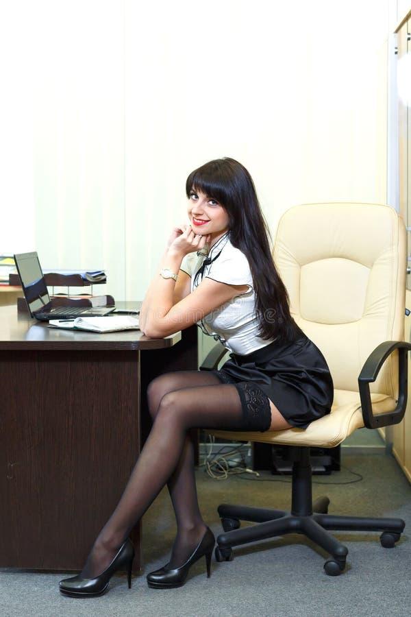 Giovane donna sexy in calze nere che si siedono sul posto di lavoro in offi fotografia stock libera da diritti