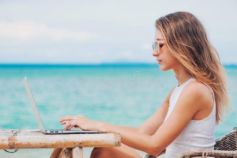 Giovane donna sexy che per mezzo del computer portatile sulla spiaggia Freelance il lavoro fotografie stock libere da diritti