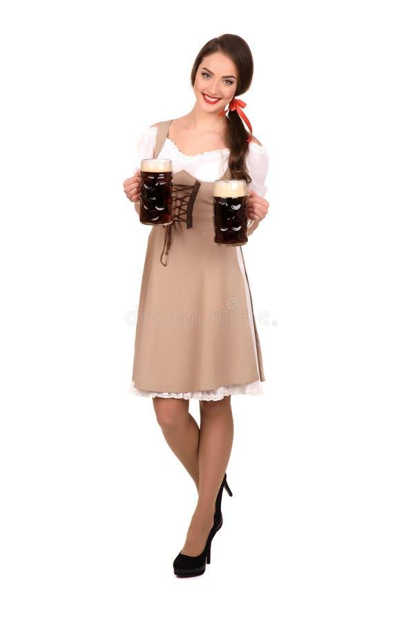 Giovane donna sexy che porta un dirndl con un isolato di due tazze di birra fotografia stock
