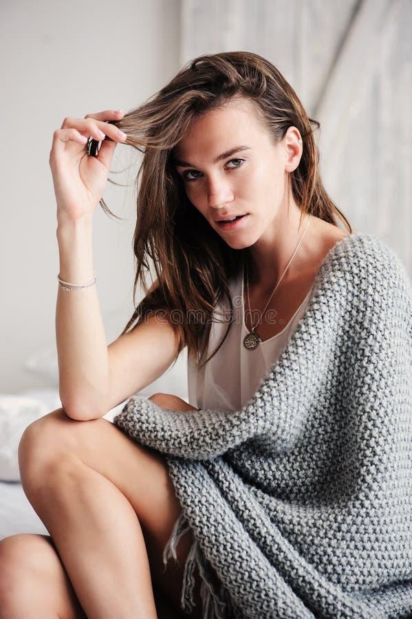 Giovane donna sexy che si rilassa a casa a letto nella mattina di fine settimana, avvolta in coperta tricottata immagini stock libere da diritti