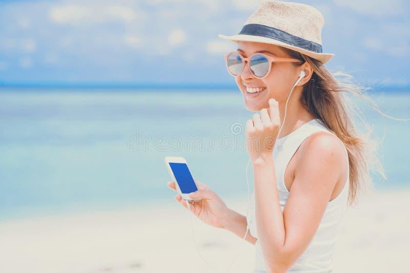 Giovane donna sexy con le cuffie facendo uso del telefono sulla spiaggia fotografia stock libera da diritti